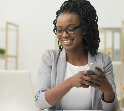 Business Chat. Positive Afro Businesswoman Texting Via Smartphone Sitting At Laptop In Modern Office.